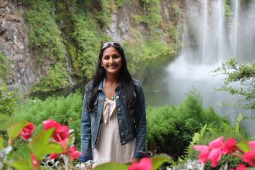 Devanshi Kothari standing in front of a waterfall.